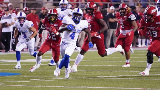 Tennessee State running back Sabree Curtis (4) tries to elude the Jacksonville State defense in Saturday's game.