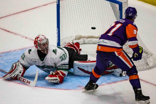 Orlando Solar Bears' Brent Pedersen hits the puck past Florida Everblades' goalie Cam Johnson for the team's second goal during a preseason game, Saturday, Oct. 5, 2019, at Hertz Arena in Estero.
