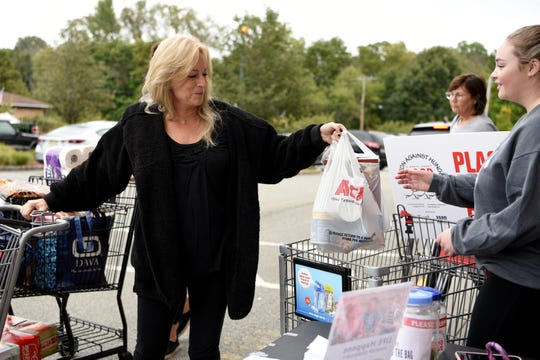 Food and money donations for the 28th Action Against Hunger Food Drive are collected outside of ACME supermarket in Allendale on October 6, 2019. Marnie McGuirk gives a food donation to Amanda Hunter, a volunteer from Ramapo College.