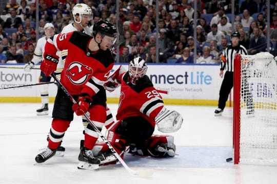 New Jersey Devils defenseman Mirco Mueller (25) and goaltender Mackenzie Blackwood (29) watch the puck enter the net during the second period of an NHL hockey game against the Buffalo Sabres, Saturday, Oct. 5, 2019, in Buffalo, N.Y.