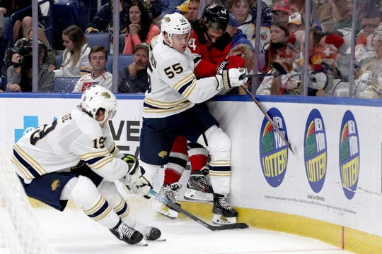 Buffalo Sabres defenseman Jake McCabe (19) attempts to take the puck as defenseman Rasmus Ristolainen (55) checks New Jersey Devils left wing Miles Wood (44) during the third period of an NHL hockey game, Saturday, Oct. 5, 2019, in Buffalo, N.Y.