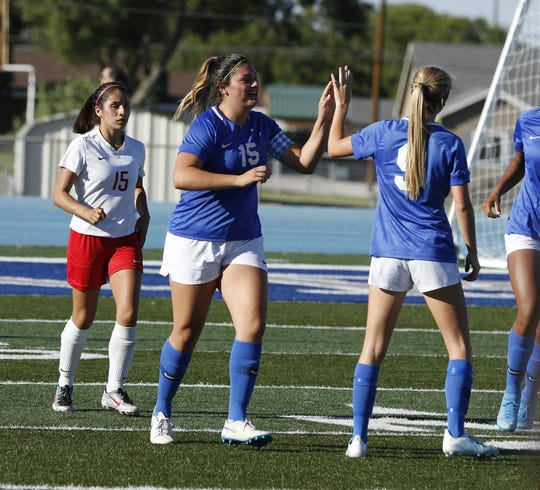 Carlsbad's Taighen Whitzel (15) gets a high-five from teammate Jessica Munro (9) after Whitzel scored her first goal of the season against Roswell on Oct. 5, 2019. Carlsbad beat Roswell, 5-0.