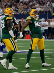 Green Bay Packers defensive tackle Montravius Adams (90) looks on as Preston Smith (91) celebrates after sacking Dallas Cowboys' Dak Prescott in the first half of an NFL football game in Arlington, Texas, Sunday, Oct. 6, 2019.