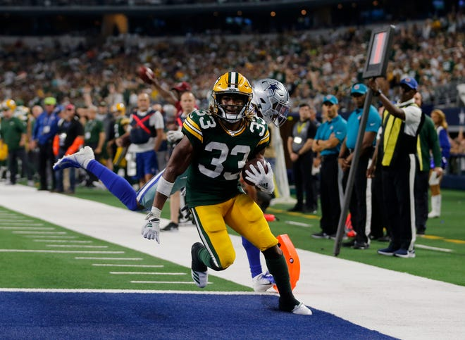 Green Bay Packers' Aaron Jones (33) reaches the end zone for a touchdown in front of Dallas Cowboys' Byron Jones, rear, in the second half of an NFL football game in Arlington, Texas, Sunday, Oct. 6, 2019.