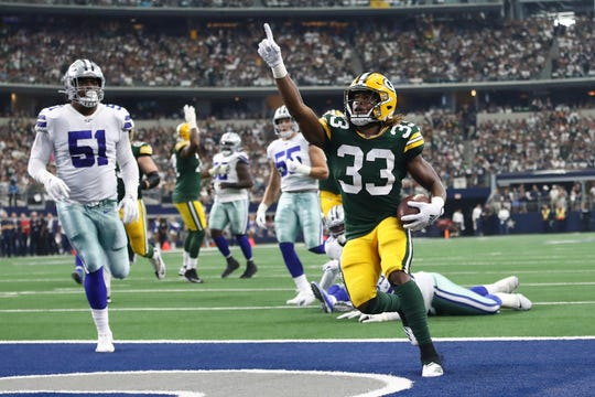 ARLINGTON, TEXAS - OCTOBER 06: Aaron Jones #33 of the Green Bay Packers celebrates after scoring on an 18-yard run against the Dallas Cowboys in the first quarter of their game at AT&T Stadium on October 06, 2019 in Arlington, Texas.