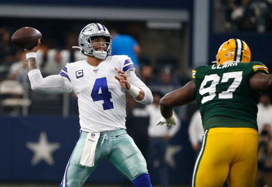 Dallas Cowboys quarterback Dak Prescott (4) throws a pass under pressure from Green Bay Packers' Kenny Clark (97) in the first half of an NFL football game in Arlington, Texas, Sunday, Oct. 6, 2019. The pass was intercepted by Chandon Sullivan.
