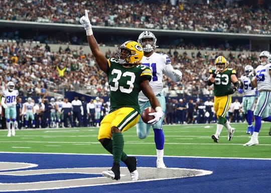 Oct 6, 2019; Arlington, TX, USA;  Green Bay Packers running back Aaron Jones (33) scores a touchdown in the first quarter against the Dallas Cowboys at AT&T Stadium.