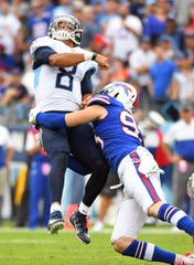Tennessee Titans quarterback Marcus Mariota (8) throws the ball as he is hit by Buffalo Bills defensive end Trent Murphy (93).