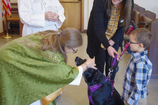 The Rev. Carren Sheldon blesses Jetta, a labrador-border collie mix, during an animal blessing Sunday in honor of the Feast of St. Francis at All Saints' Episcopal Church in Redding