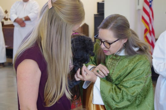 Jill Villalobos watches as The Rev. Carren Sheldon, interim rector at All Saints' Episcopal Church in Redding, blesses Roxie, a miniature goldendoodle. The church held an animal blessing Sunday as part of the Feast of St. Francis.