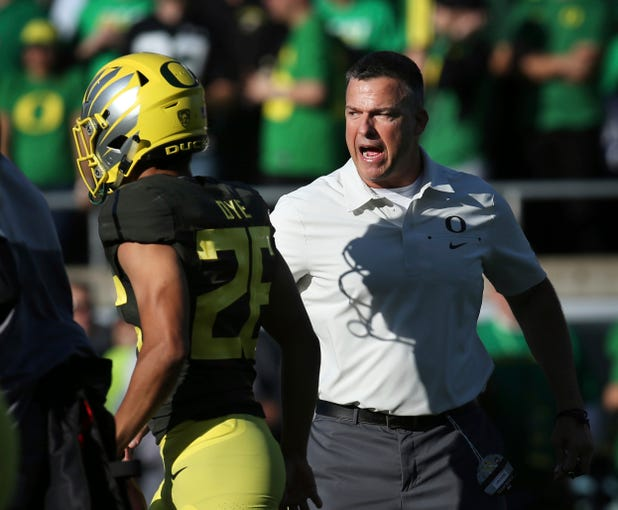 Oregon head football coach Mario Cristobal, right, yells encouragement to his team during warm ups before their NCAA college football game against California, Oct.. 5, 2019, in Eugene, Ore.