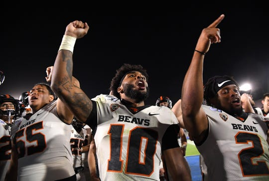 Oct 5, 2019; Pasadena, CA, USA; Oregon State Beavers offensive lineman Onesimus Clarke (65), tight end Isaiah Smalls (10) and defensive back Shawn Wilson celebrate after defeating the UCLA Bruins at the Rose Bowl. Mandatory Credit: Jayne Kamin-Oncea-USA TODAY Sports