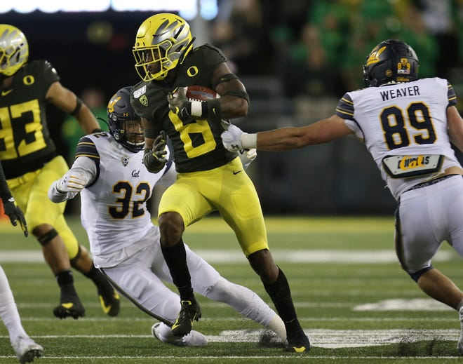 Oregon's Jevon Holland runs between California's Daniel Scott, left, and Evan Weaver, right, during the third quarter of an NCAA college football game, Oct. 5, 2019, in Eugene, Ore.