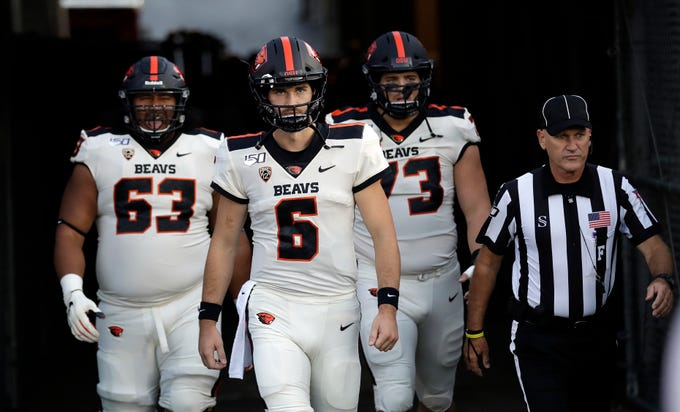 Oregon State quarterback Jake Luton (6) enters the field with teammates Gus Lavaka, left, and Blake Brandel before an NCAA college football game against UCLA, Oct. 5, 2019, in Pasadena, Calif.