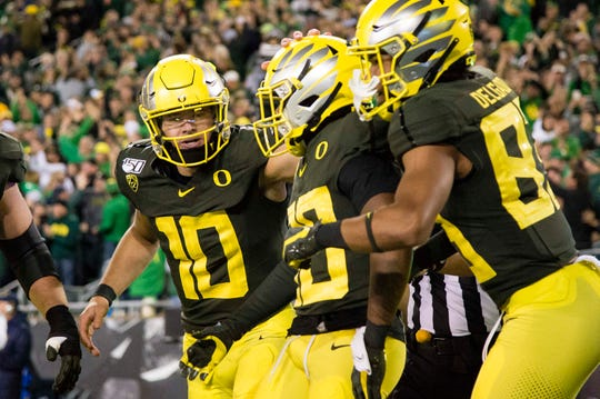 Oct 5, 2019; Eugene, OR, USA; Oregon Ducks quarterback Justin Herbert (10) celebrates a touchdown by wide receiver Jaylon Redd (30) during the second half at Autzen Stadium. Oregon won the game 17-7. Mandatory Credit: Troy Wayrynen-USA TODAY Sports