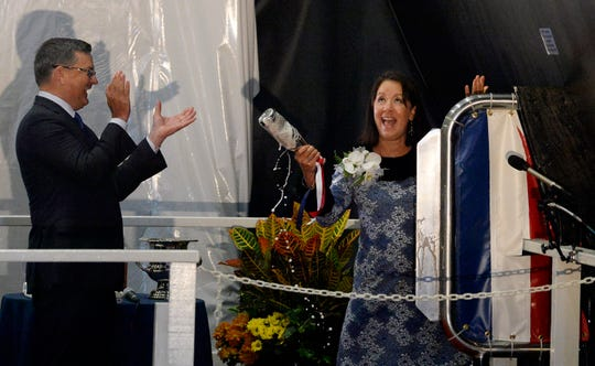 Sponsor Dana Richardson, right, reacts after successfully breaking the bottle on the second try with Kevin Graney, president of General Dynamics Electric Boat, looking on during the christening ceremony for the U.S. Navy's newest attack submarine, the future USS Oregon, at Electric Boat shipyard in Groton, Conn., Saturday, Oct. 5, 2019. Richardson, a native of Corvallis, Ore., said the privilege of being a ship sponsor is beyond her wildest dreams. She's married to retired Adm. John Richardson, who served as the chief of naval operations from 2015 until this summer.
