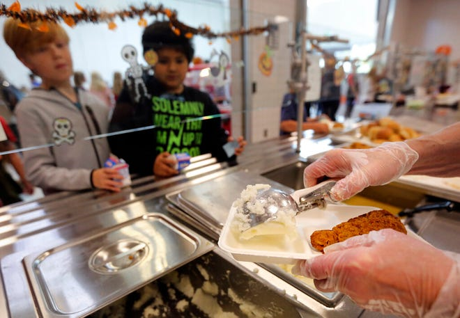 Deborah Hut dishes out lunch on a compostable tray at Butler Elementary School in Cottonwood Heights, Utah on Wednesday, Oct. 2, 2019.  (Kristin Murphy/The Deseret News via AP)