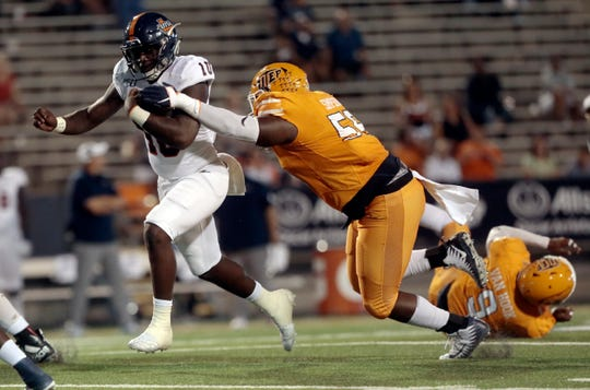 UTEP tackle Dedrick Simpson goes for the strip as UTSA quarterback Lowell Marcisse takes off on a keeper on Oct. 5 at the Sun Bowl.