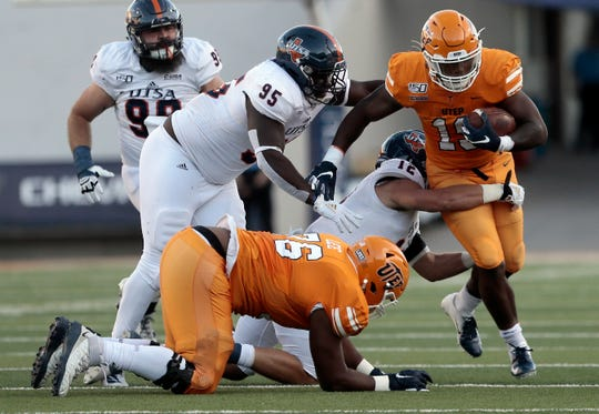 UTEP running back Treyvon Huges looks for running room around UTSA defenders Saturday.