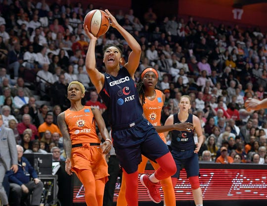 Washington Mystics' Aerial Powers, center, breaks past Connecticut Sun's Courtney Williams, left, and Jonquel Jones, right, for a layup during the second half in Game 3 of basketball's WNBA Finals, Sunday.