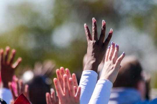 Moments of silence and other tributes to former Woodbridge High quarterback Troy Haynes were held around the state during high school football games this week. Here, fans hold up four fingers to symbolize Haynes' jersey number before the St. Georges at William Penn game on Saturday in New Castle.