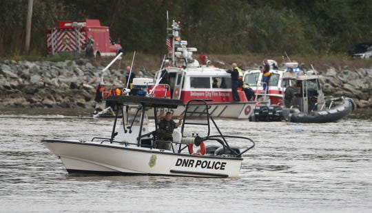 A police officer tries to slow passing boat traffic as emergency personnel, including divers, work on the C&D Canal where a vehicle plunged into the water from South Canal Road west of the Roth Bridge Sunday morning.