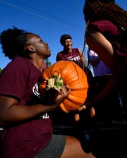Jada Morris laughs as Taya Bridges momentarily sinks under the weight of a hefty pumpkin during offloading at Disability Resources, Inc. Wednesday. The McMurry women's basketball team were one of the volunteer groups helping set up the patch.
