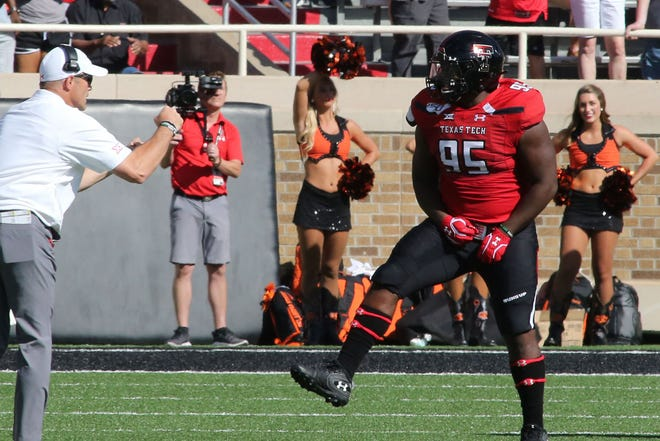 Oct 5, 2019; Lubbock, TX, USA; Texas Tech Red Raiders head coach Matt Wells (left) congratulates defensive tackle Jaylon Hutchings (95) on a play against the Oklahoma State Cowboys at Jones AT&T Stadium. Mandatory Credit: Michael C. Johnson-USA TODAY Sports