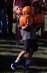 Cooper Roes, 6, carefully watches where he steps as he balances three pumpkins Wednesday at Disability Resources, Inc. At least two hundred volunteers and others unloaded the gourds for the annual DRI Pumpkin Patch which runs for the rest of the month.