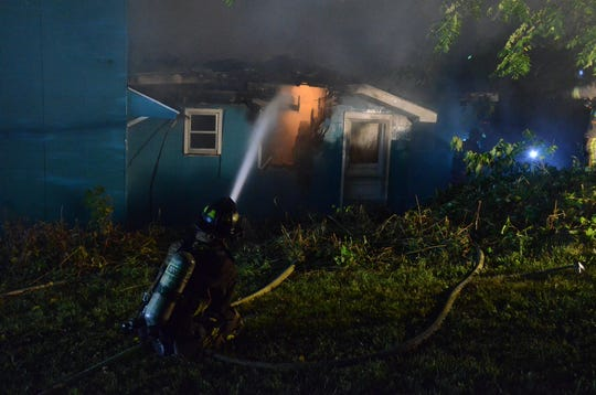 A firefighter attacks flames at the back of a house on West Fountain Street in September.