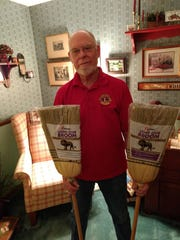 Richard Barron, of Berkshire, displays brooms that are handmade by people who are blind and are sold to benefit the charitable projects done by the Binghamton Lions Club. Barron has been a member of Lions Club International for 48 years.