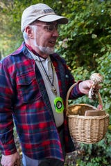 David Ansley observes a shaggy parasol during the Kitsap Peninsula Mycological Society's excursion on Oct. 5.