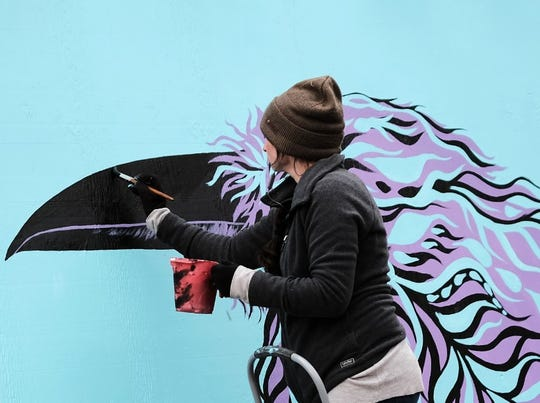 Nikki Laxar, one of the artists taking part in the Bank Street Block Party in Burlington, puts the finishing touches on her mural on Friday, Oct. 4, 2019. When the pieces were completed, the murals painted by the artists were mounted on the blue barrier surrounding the CityPlace Burlington construction area. The event was organized by the city's Community and Economic Development Office  and Burlington City Arts.