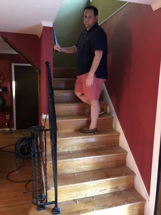 Ron Gallo stands on the steps of his Cherry Hill home. Just days before, rainwater ran from the second floor down those stairs after a tree crashed through the home.