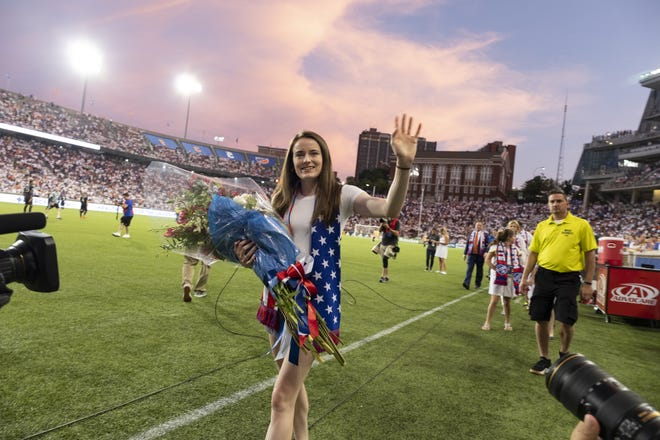 Rose Lavelle waves to fans during halftime of the MLS soccer match between FC Cincinnati and DC United on Thursday, July 18, 2019 in Cincinnati.