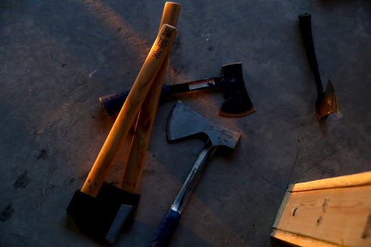 Various axes that will be provided for throwing can be seen laying on the ground for photographic purposes at The Axe Throwing Place in Clarksville, Tenn., on Wednesday, Oct. 2, 2019.