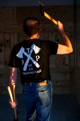 Henry Walker winds his arm back to perform a throw at The Axe Throwing Place in Clarksville, Tenn., on Wednesday, Oct. 2, 2019.