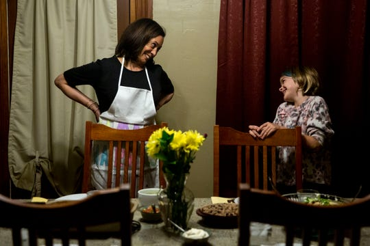 U.S. Sen. Kamala Harris, D-CA, smiles at 10-year-old Jane Grimm while setting the table for a Sunday night dinner with Jane's family on Sunday, Oct. 6, 2019, in Ames.