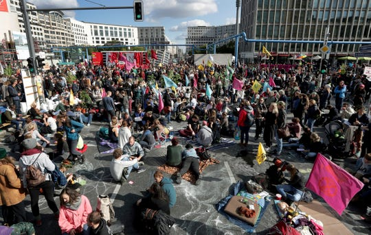 Supporters of the 'Extinction Rebellion' movement block a road at the Potsdamer Platz square in Berlin, Germany, Monday, Oct. 7, 2019.