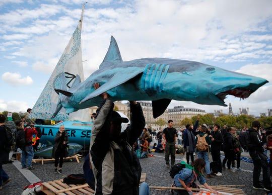 Activists from Extinction Rebellion block a bridge Monday, Oct. 7, 2019 in Paris.
