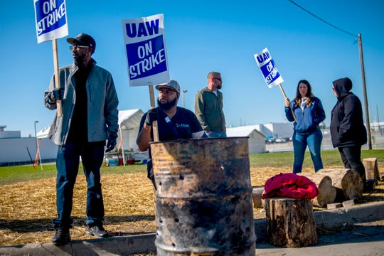Detroit resident Jay Hawkins, left, and Flint resident Damien Moore picket outside of General Motors' Flint Paint Facility during the nationwide UAW strike against General Motors on Monday in Flint, Mich. Hawkins has 12 years in at the Flint Assembly Plant, while Moore has 11 months in as a temporary worker.