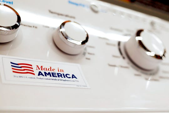 In this May 9, 2019, file photo a General Electric washing machine with a label advertising it was made in America is displayed in retail stores in Cranberry Township, Pa. General Electric Co. said Monday, Oct. 7, that it will freeze its pension plan for about 20,700 salaried workers as part of its debt-cutting plan.
