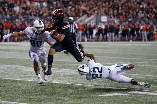 Ohio State quarterback Justin Fields tries to slip past Michigan State defensive lineman Jacub Panasiuk, left, and defensive back Josiah Scott.