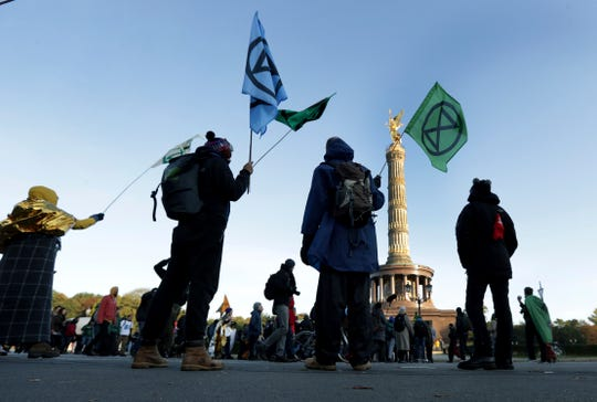 Supporters of the 'Extinction Rebellion' movement block a road at the Victory Column in Berlin, Germany, Monday, Oct. 7, 2019.