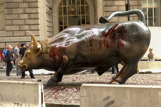 "Stage blood covers the iconic ""Charging Bull"" statue near Wall Street on Monday Oct. 7, 2019, in New York. Demonstrators say they were protesting against a lack of government action against climate change."