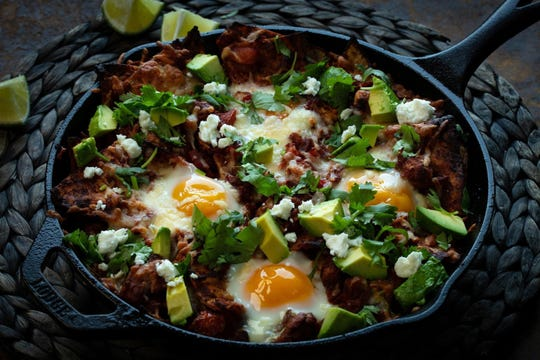 Eggs bake directly in the tortilla chip and tomato sauce mixture. After coming from the oven, the chilaquiles is garnished with avocado, feta and cilantro.