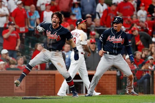 Atlanta Braves' Dansby Swanson, left, and Rafael Ortega, right, celebrate after scoring as St. Louis Cardinals relief pitcher Carlos Martinez (18) walks in the background during the ninth inning in Game 3 of a baseball National League Division Series on Sunday in St. Louis.