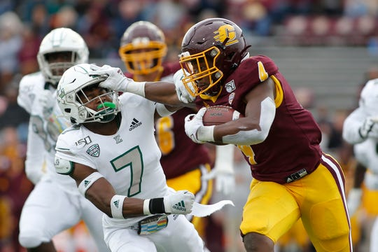 Central Michigan's Kobe Lewis stiff-arms Eastern Michigan's Freddie McGee III during their game on Saturday.