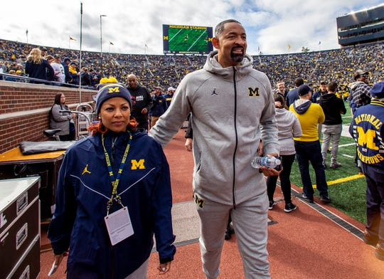 Michigan basketball coach Juwan Howard and wife Jenine Wardally walk the sidelines at Michigan Stadium before the game against Iowa.