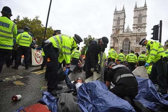 Police remove demonstrators participating in the Extinction Rebellion protest in London, Monday, Oct. 7, 2019.